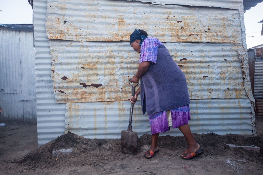 A resident builds a berm around her home to reduce flooding risk. Photo by Shachaf Polakow.