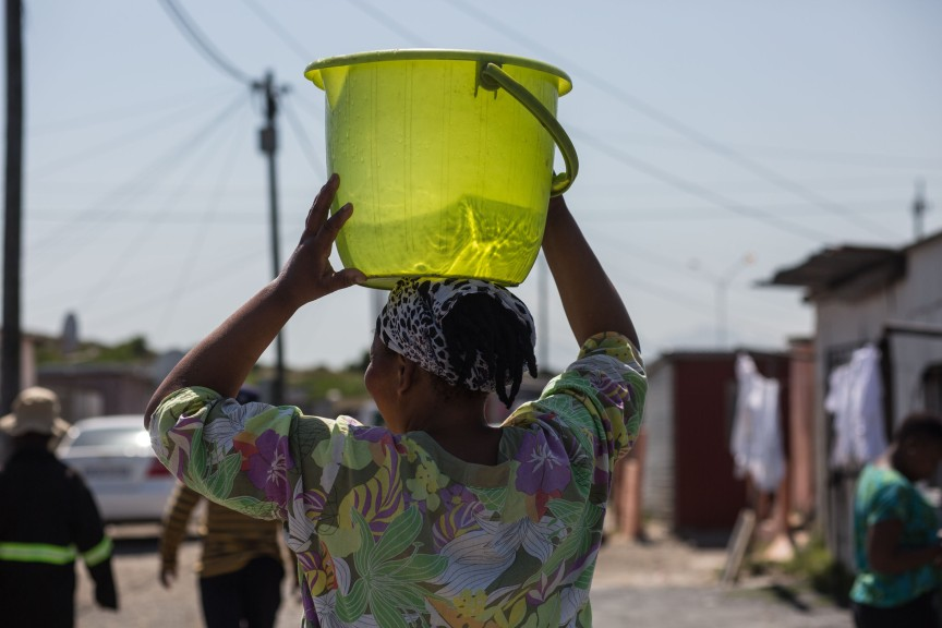 A resident walking with water from a tap back to her home. Despite promised upgrading for more than fifteen years, residents on this site still rely upon only a few shared taps. Photo by Shachaf Polakow.