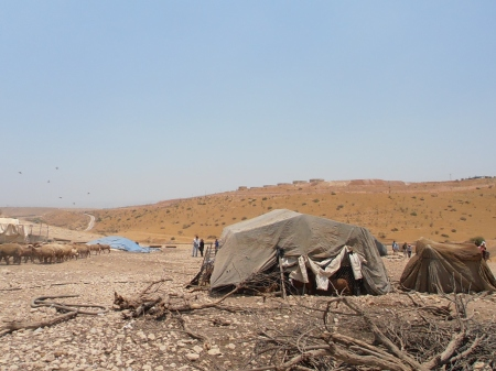 Palestinians displaced by the settlement, visible as concrete structures in the background
