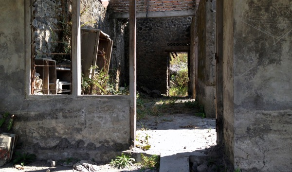 Figure 15. A ruined and vacated house near the volcano Merapi in Indonesia. Merapi is considered the world's most dangerous volcano, and it erupts frequently. Nonetheless, people continue to settle close by, because previous eruptions have made valuable raw materials available. The owner of the house lost his wife and child in a Merapi eruption and now works in a near-by sand mine. Photo by Felix Riede.