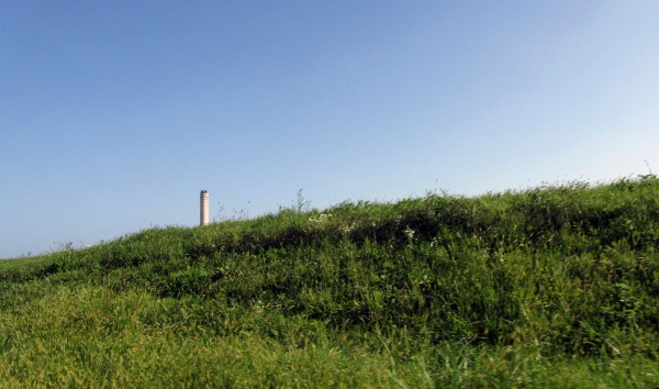 Figure 13. Behind the dike surrounding the Po delta in Italy, the chimney of a decommissioned power station marks the industrialization of the area. The dikes have to be continuously maintained since the delta area sunk up to five metres below sea level after methane extraction in the 1960s.This has made the delta much more at risk of flooding, which has led to a rural exodus. In the event of future sea level rise the delta is further exposed. Photo by Meredith Root-Bernstein.